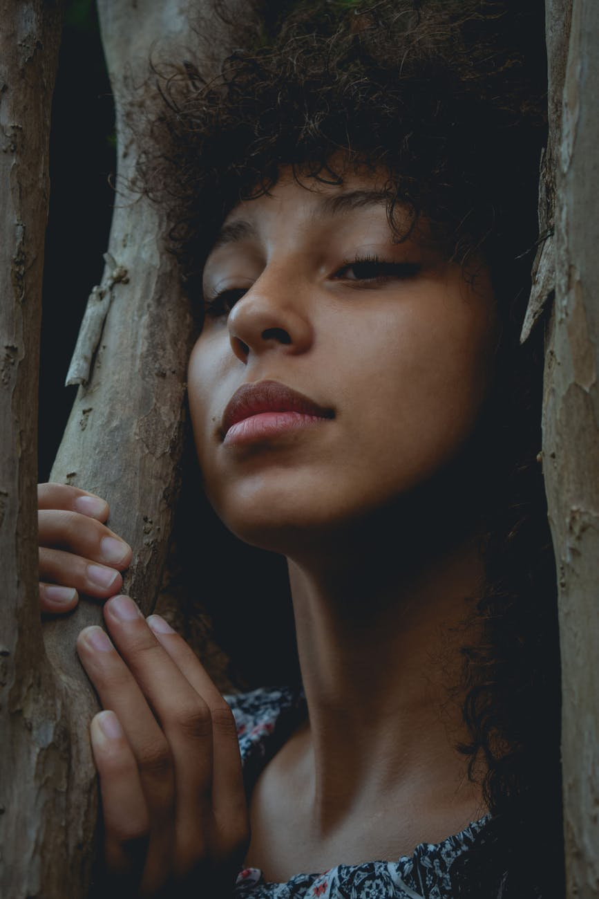 close up photo of a woman in between woods
